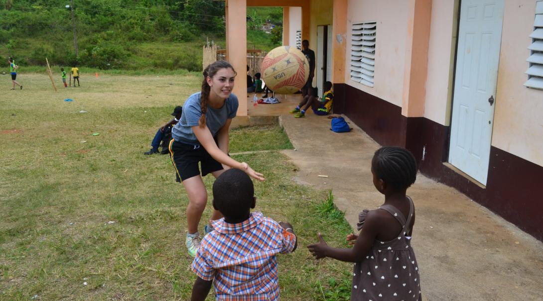 Une volontaire en chantier jeune enseigne la coordination œil-main à des enfants jamaïcains, à l'aide d'un ballon.